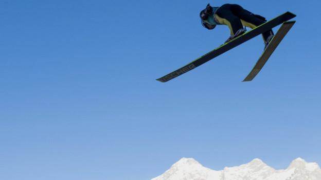 Ein Skispringer fliegt durch die Luft.