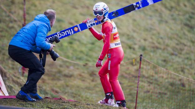 Ein Skispringer mit Skieren läuft über Gras.