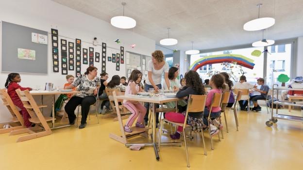 Kinder und Betreuungspersonen in einem Raum.