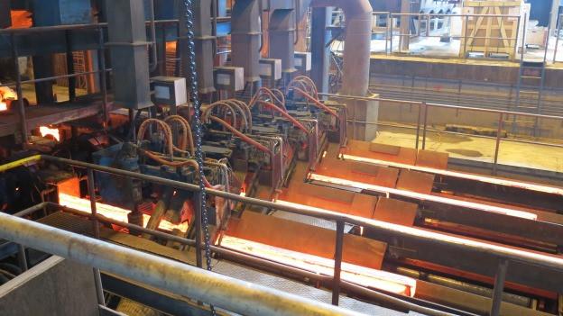 Stahlproduktion in einer Fabrikhalle.
