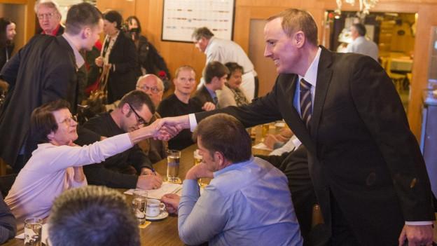 Politiker begrüsst Anwesende an einer Versammlung.