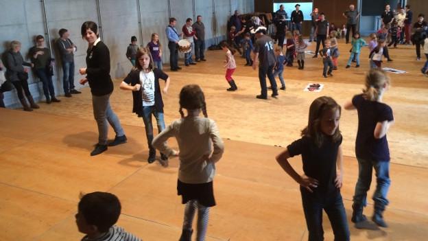 Kinder in einer Halle am Nüsseln.