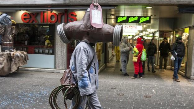 Ein Fasnächtler mit einer Wasserhahn-Maske läuft durch die Stadt Luzern.