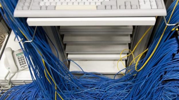 Eine Computer-Tastatur und viele blaue Kabel.