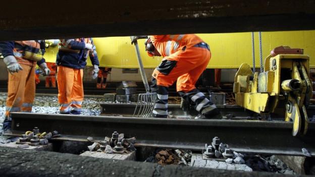 Gleisarbeiter entfernen Bahnschienen.
