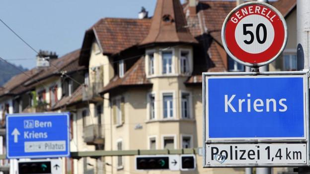 Ortstafel von Kriens und eine Häuserreihe.