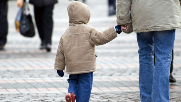 Kind wird an der Hand geführt auf einem Spaziergang.