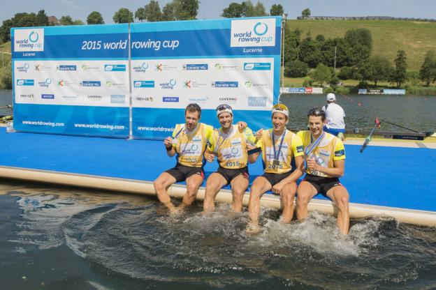 Vier Ruderer mit Silbermedaille sitzen auf einem Steg und halten die Füsse ins Wasser.