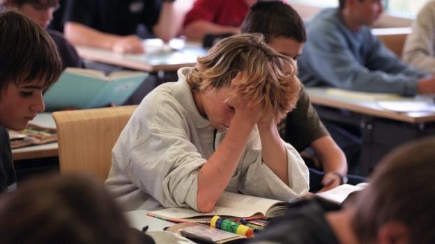 Schüler an einem Pult in einem Schulzimmer.