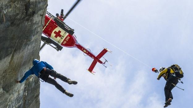 Ein Rega-Helikopter rettet einen Kletterer aus einer Wand.