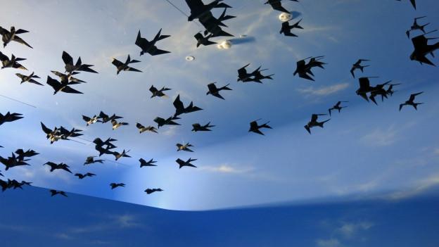 Origami-Vögel vor einem künstlichen blauen Himmel.