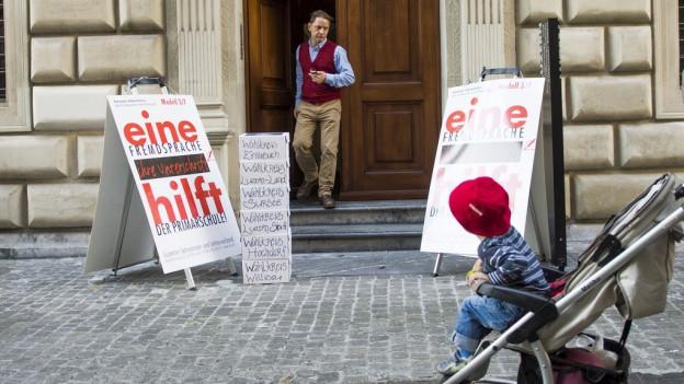 Ein Plakat und ein Kinderwagen vor dem Luzerner Regierungsgebäude.
