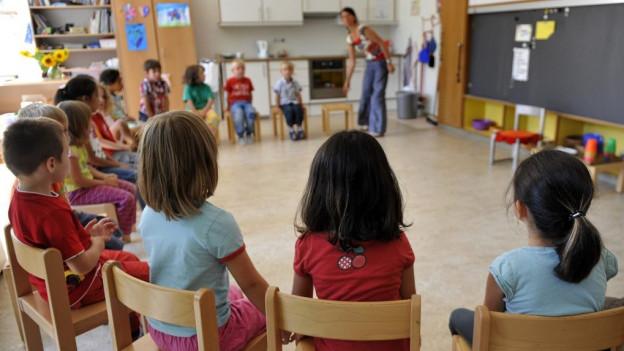 Kindergartenkinder sitzen in einem Kreis.