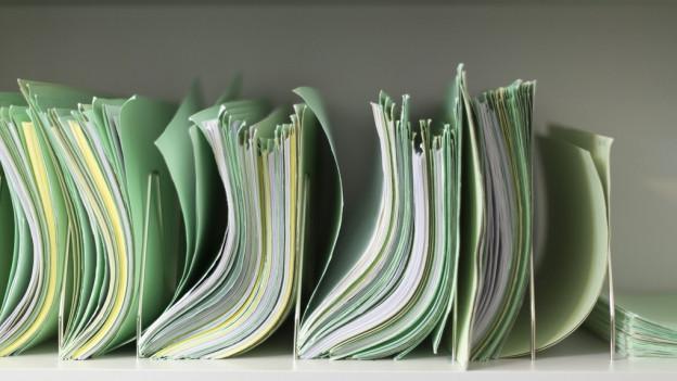 Akten in grünen Hängeregistern.