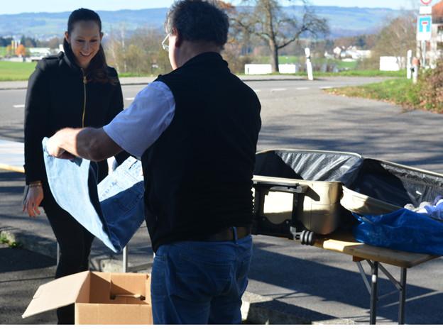 Eine Mitarbeiterin der Gemeinwesenarbeit nimmt Kleiderspenden entgegen.