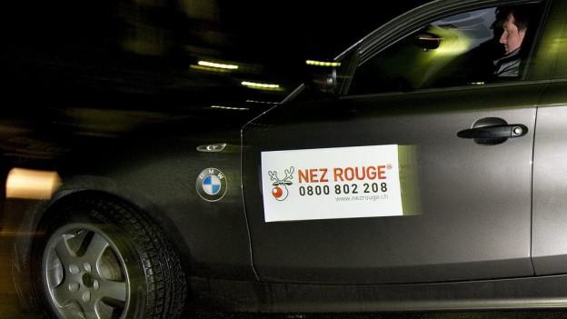 Ein Auto der Aktion Nez Rouge fährt durch die Nacht.