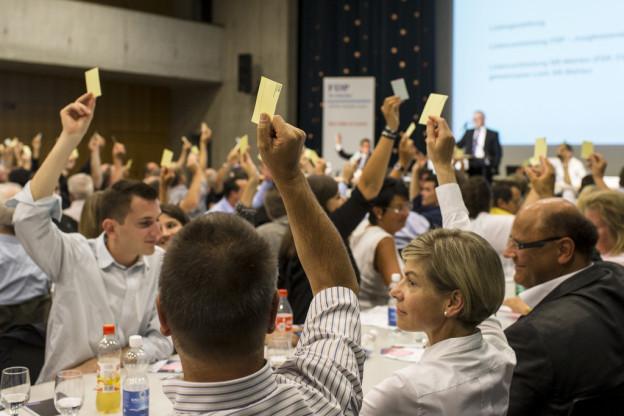 Politiker sitzen an einem Tisch und erheben gelbe Karten bei einer Abstimmung.