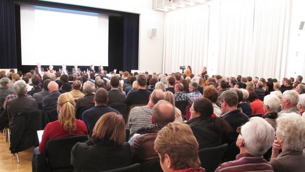 Ein Saal voller Leute während einer Informationsveranstaltung.