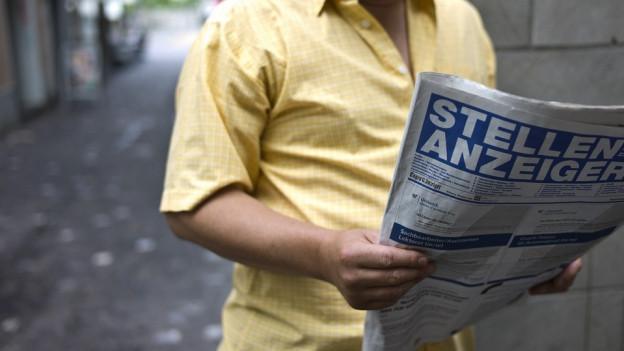 Mann mit Zeitung in der Hand.