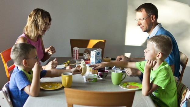Eine Familie sitzt am Tisch und isst.