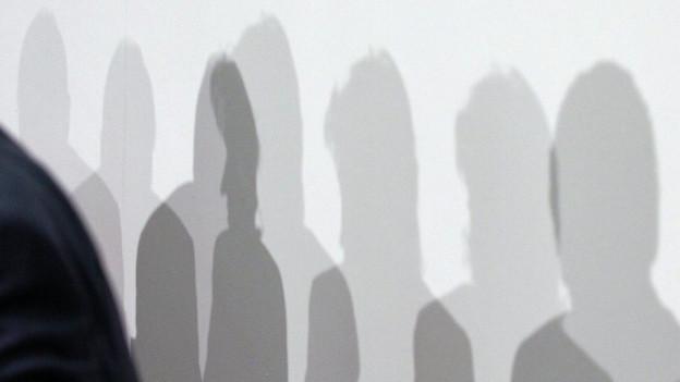 Eine Wand mit einer Reihe von Schatten von Menschen.