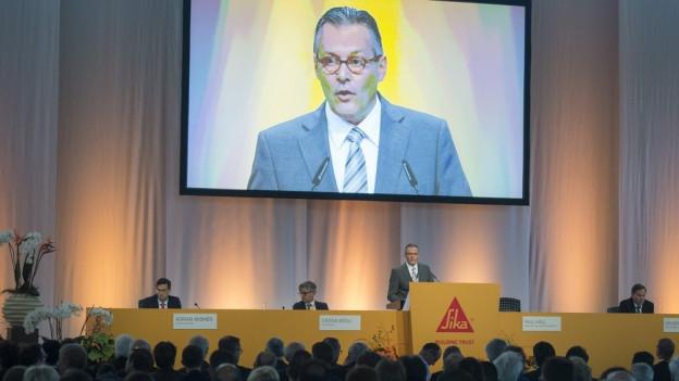 Grosser Bildschirm mit Verwaltungsratspräsidenten an einer Generalversammlung.