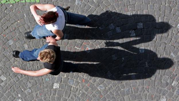 Ein homosexuelles Paar spaziert händehaltend über einen Platz.