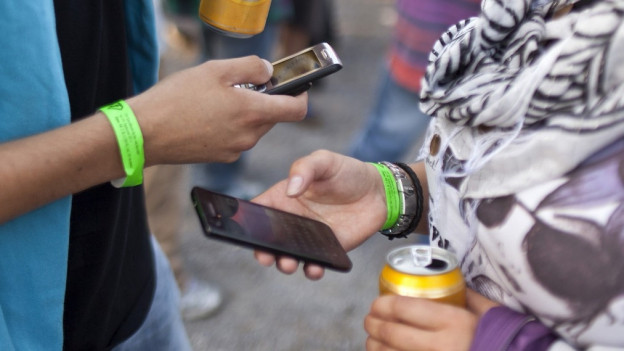 Jugendliche drücken auf ihrem Smartphone herum.