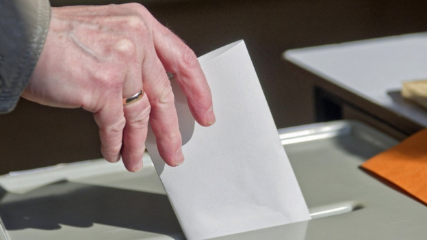 Wähler wirft seinen Stimmzettel ein.