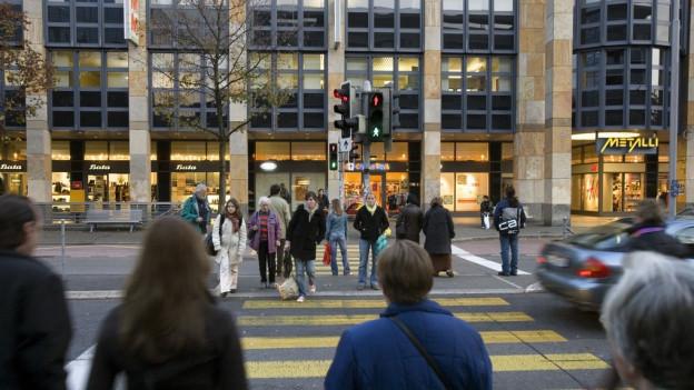Fussgaenger stehen an einer Ampel an einer Strasse.
