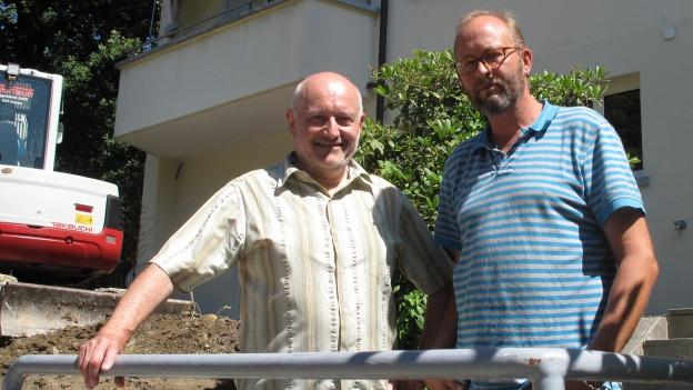 Zwei Männer stehen vor einem Haus.