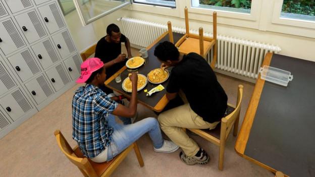 Asylsuchende in einer Unterkunft beim Essen.