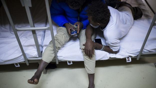 Zwei Asylbewerber sitzen auf einem Bett.