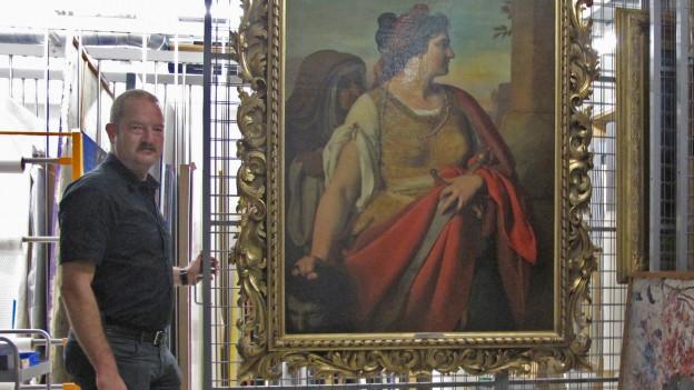 Eine Mann steht vor einem Gemälde, das eine Frau zeigt.