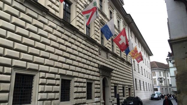 Gebäude mit Fahnen an der Fassade.