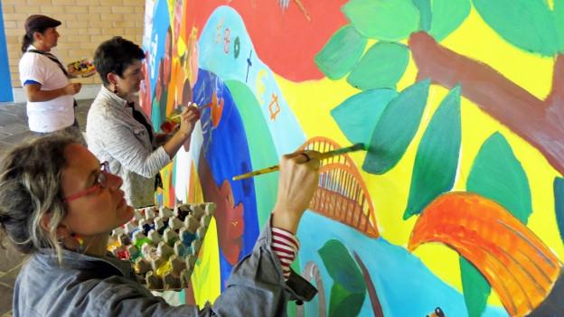 Zwei Frauen malen an einem grossen Wandbild.