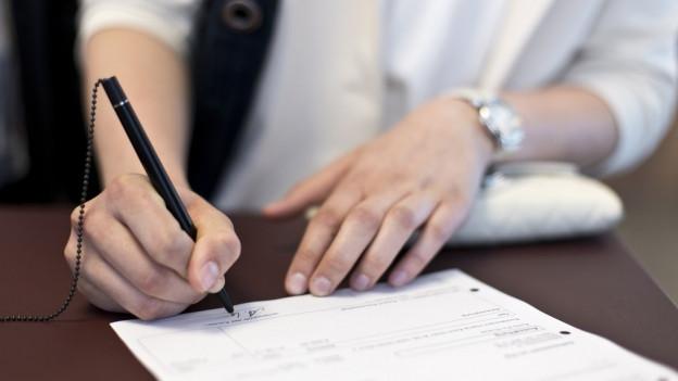 Frau unterschreibt Dokument