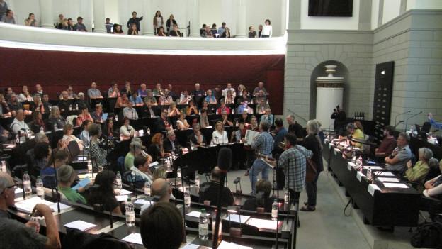 Menschen diskutieren in einem Parlamentssaal.