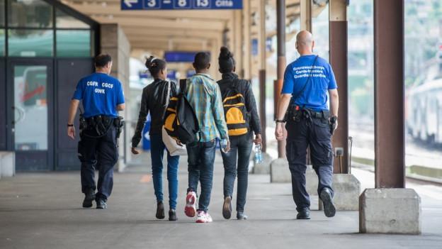 Polizisten begleiten Flüchtlinge an einem Bahnhof.