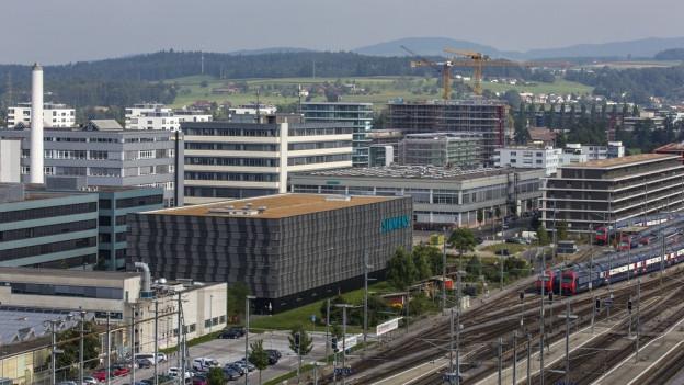 Die Stadt Zug aus der Vogelperspektive mit Gleisen und Bauten.