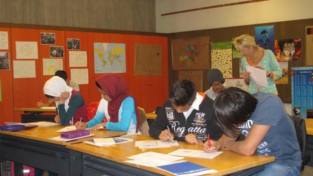 Schülerinnen und Schüler sitzen an Pulten und schreiben in Hefte.