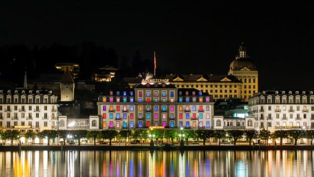 Ein Hotel in Luzern mit farbigen Fenstern in der Nacht.