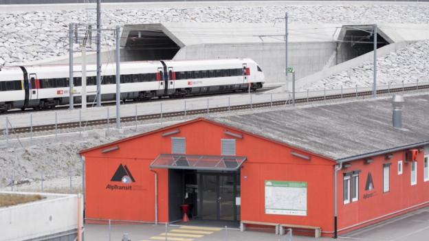 Zug fährt in Erstfeld neben Besucherzentrum in Basistunnel.