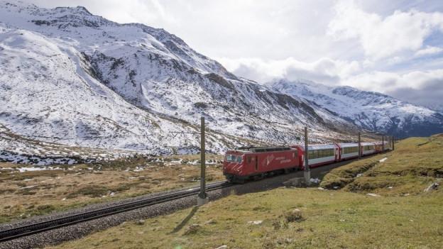 Ein roter Zug fährt vor einem Bergpanorama durch.