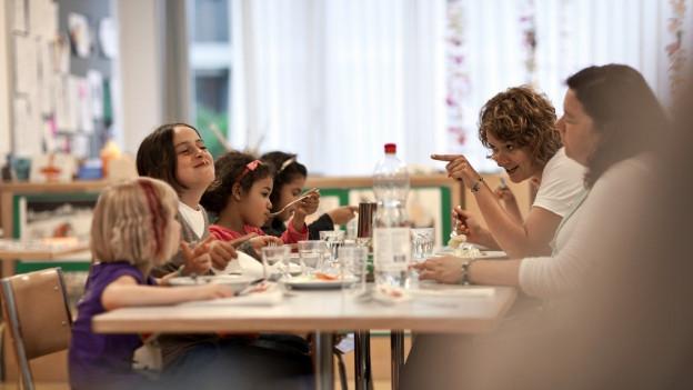 Kinder essen in einer Kindertagesstätte.