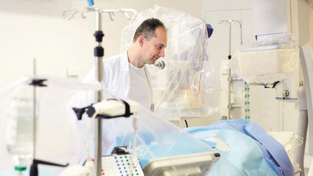 Arzt schaut nach einem Patienten in einem Bett.
