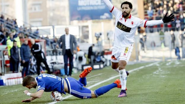 Ein Spieler des FC Luzern liegt auf dem Boden, ein Spieler von Sion hebt die Hände.