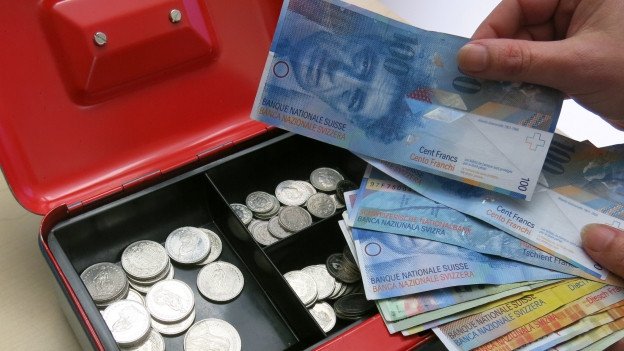 Jemand nimmt Geld aus einer vollen Kasse.