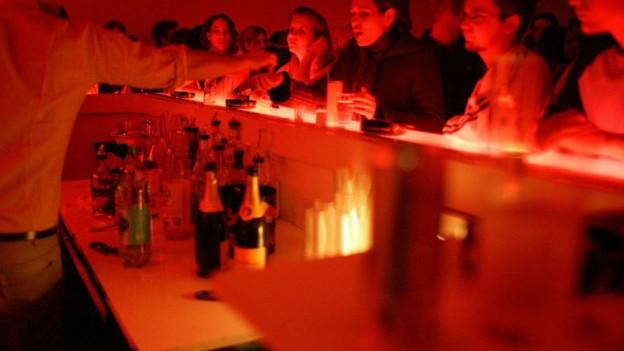 Junge Menschen trinken an einer Bar.