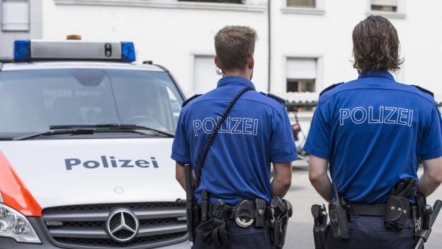 Polizisten stehen vor einem Polizeiauto.